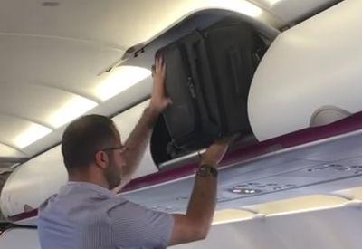 Harter Kampf mit dem Gepäckfach im Flugzeug